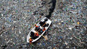 une barque au milieu d'une eau rempli de plastique