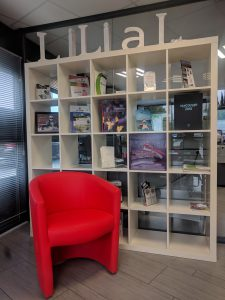 Entrée de Lilial, étagères avec des livres, fauteuil rouge devant
