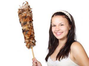 femme souriante un plumeau de ménage marron à la main