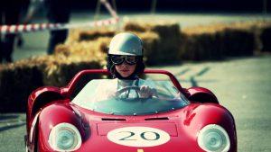 Un enfant avec de lunettes noires et un casque au volant d'une mini voitrue roueg avec le chiffre 20 écrit sur le capot