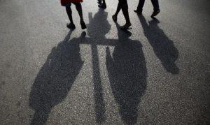 Quatre paird jambes habillés et leurs ombres autour de l'ombre d'une croix