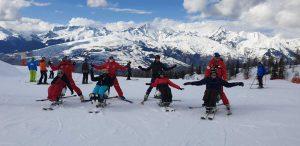 personne dans des dual ski e ttandem ski avec leurs accompagnateurs derrière